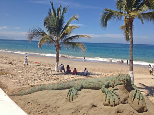 Palms onbeach and Iguana sand sculpture along Malecon in Puerto Vallarta, Mexico