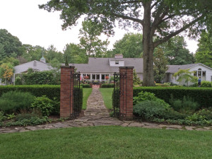 Framing of entrance with brick pillars and iron gate