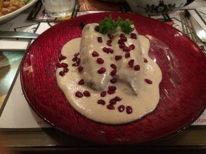 Chiles en nogada: Minced chicken and fruit in a poblano chile, covered with a creamy walnut sauce, sprinkled with pomegranate seeds, and served cold.