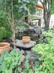 Pool into which water from downspout drains, stream above it, fountains above stream  -  prevents storm water runoff