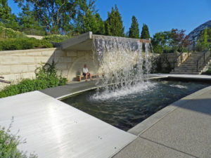 Modernistic waterfall with long bench below at Des Moines Botanical Garden